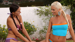 Deny and Iris - Fresh faced teens Deny, black hair, and blonde Iris kiss passionately on a blanket in the garden, then strip off their tops and fondle and suck each other's tits and nipples. They strip completely and Deny tongues Iris' tight ass