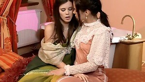 Caprice and Krissy - Gorgeous brunette Caprice in green dress and cute teen Krissy embrace and kiss tenderly on a divan in the bathroom, then they pull down their dresses to fondle and suck one anothers' firm breasts. They help each other off with th
