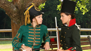 Juliette and Deny - Stunning teen Deny, darker hair, is sitting on a bench dressed in antique army clothes, when luscious minx Juliette, green antique jacket approaches her. They are tired from reenacting historic battles, so Juliette sits beside Deny and