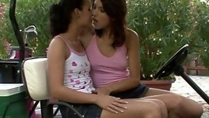 Anne and Lulu - Alluring teen Anne, wearing a pink shirt, and Lulu, in white, kiss and caress deeply in a golf cart on the eighteenth hole, then lustily take off their tops to fondle and suck each other's firm melons. They take off their minis, flick
